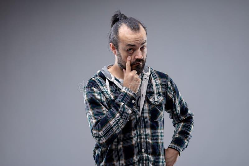 Brodaty mężczyzna z ponytail ciągnięcia puszkiem powieka obraz royalty free