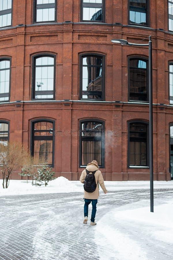 Brodaty młody człowiek dymi papieros w zimie fotografia royalty free