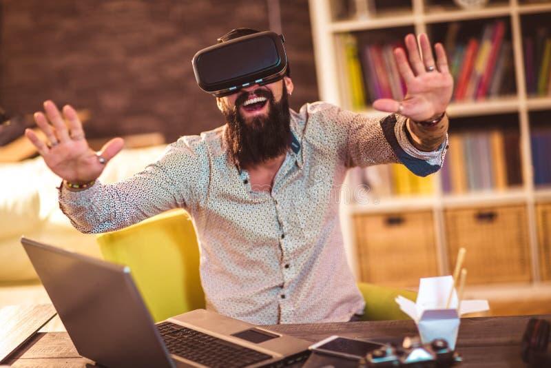 Brodaty młody człowiek jest ubranym rzeczywistość wirtualna gogle zdjęcie royalty free