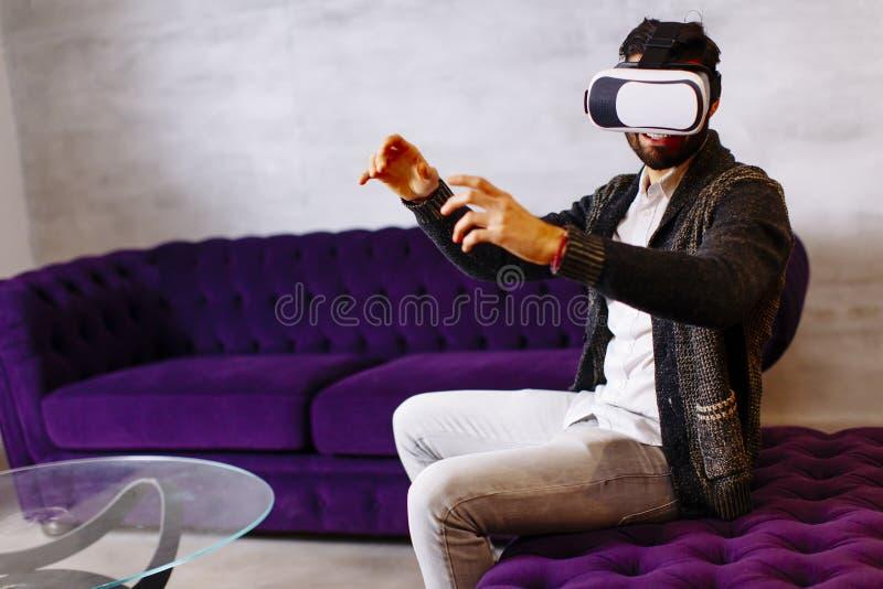 Brodaty młody człowiek jest ubranym rzeczywistość wirtualna gogle w nowożytnym pokoju zdjęcie stock