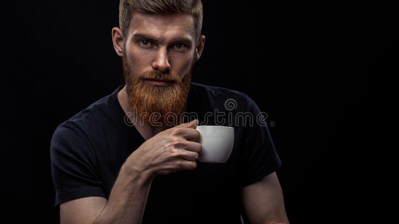 Brodaty młody człowiek pije kawę espresso obrazy royalty free