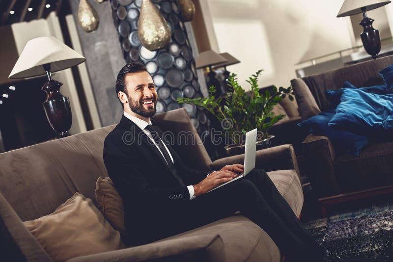 Brodaty młodzieniec uśmiecha się siedząc na kanapie z nowoczesnym urządzeniem fotografia royalty free