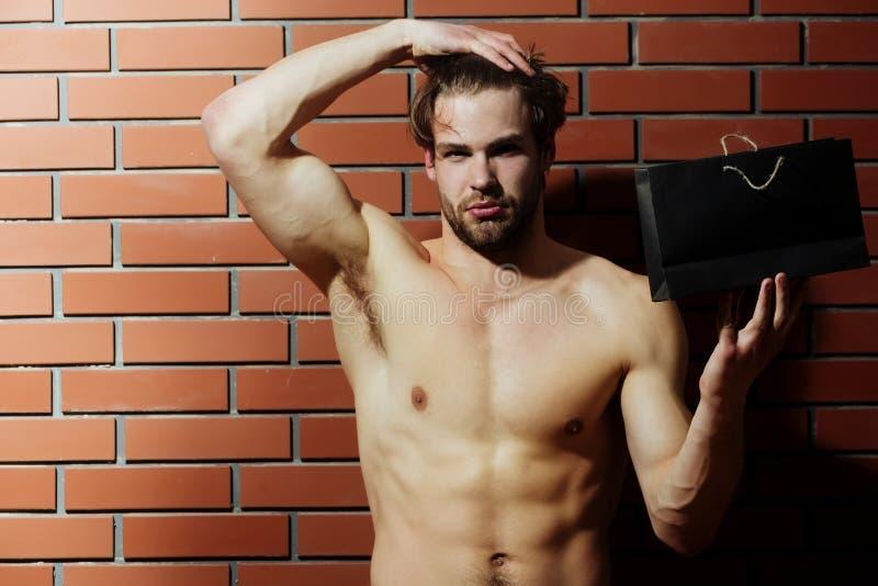Brodaty mięśniowy mężczyzna z seksownym ciałem trzyma torba na zakupy, pakunek zdjęcia royalty free