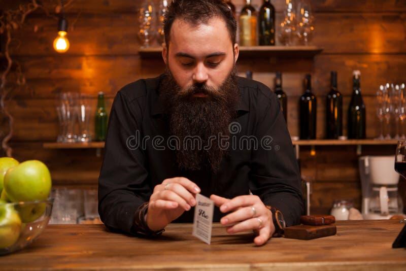 Brodaty modnisia barman bawi? si? z jego trikowymi kartami obraz stock