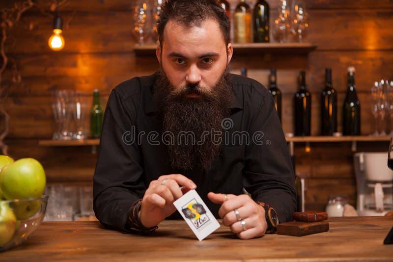 Brodaty modnisia barman bawi? si? z jego trikowymi kartami zdjęcia stock