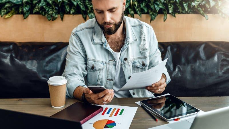 Brodaty modnisia biznesmen pracuje z dokumentami w nowożytnym biurze Mężczyzna używa smartphone, pisać na maszynie wiadomość na t obrazy royalty free