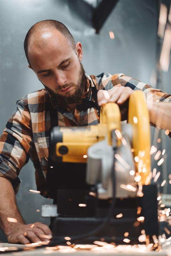 Brodaty pracownika mechanik używa elektryczną graniastą szlifierską maszynę w metalworking Praca w akci Iskry latają oddzielnie zdjęcie stock
