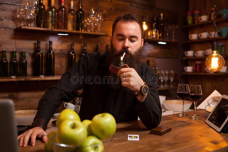 Brodaty przystojny młody barman zaświeca jego papieros zdjęcia stock