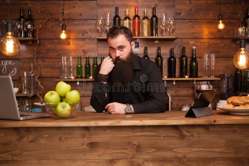 Brodaty przystojny młody barman za prętowym kontuarem zdjęcia stock