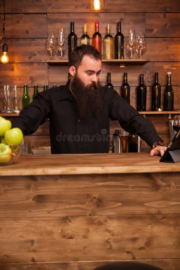 Brodaty przystojny m?ody barman za pr?towym kontuarem zdjęcie stock