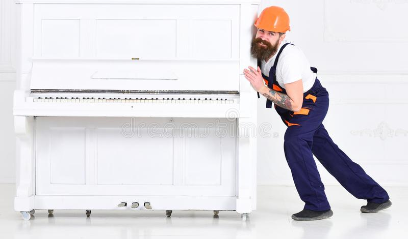 Brodaty silnego mężczyzna chylenie podczas gdy próbujący ruszać się ciężkiego pianino z otwartą klawiatury i szkła wazą Uśmiechni fotografia royalty free