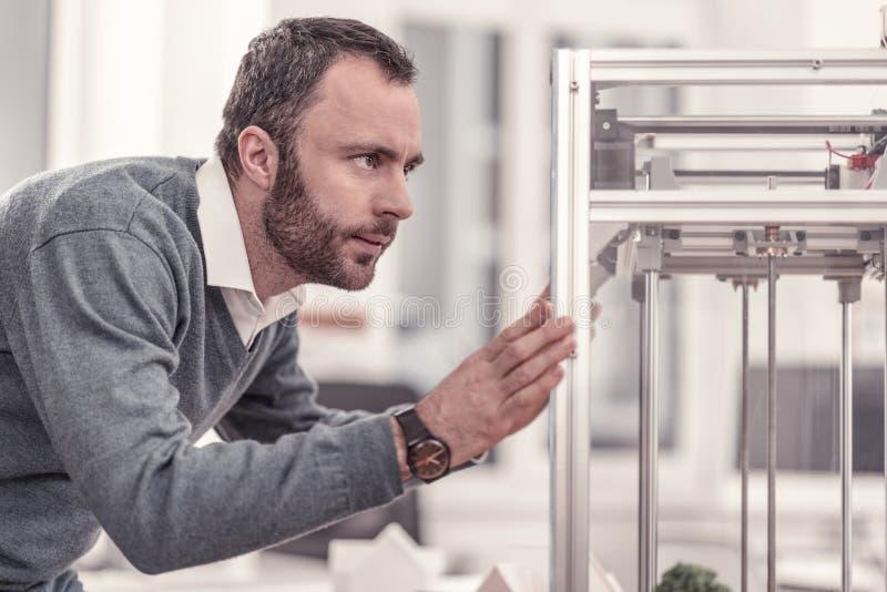 Brodaty skoncentrowany dorosły mężczyzna dopatrywanie przy 3D drukarką zdjęcia stock