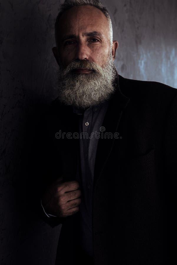Brodaty starszy mężczyzna w żakiecie pozuje w ciemnym pracownianym tła spojrzeniu obrazy stock