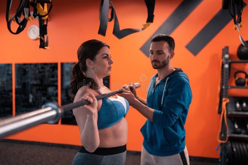 Brodaty trener pomaga tłuściuchnej kobiety z podnośnym barbell zdjęcie royalty free