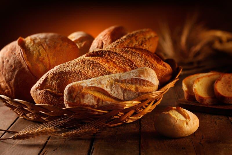 Broden van artisanaal brood met mand en oren stock afbeelding