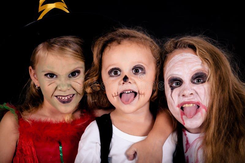 Broder och två systrar på allhelgonaafton fotografering för bildbyråer