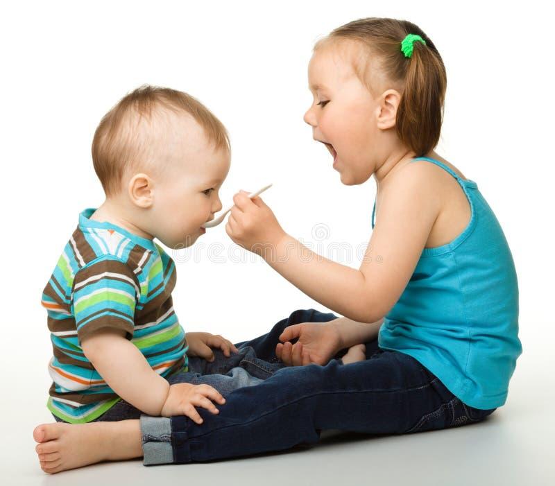 broder som matar henne den små systern arkivfoton