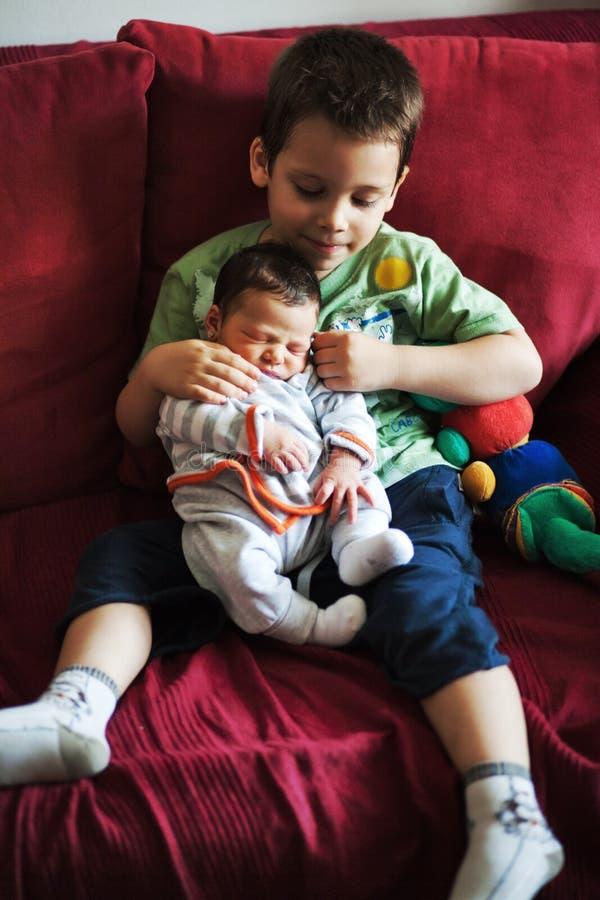 Broder som rymmer hans syster i hans armar arkivfoto