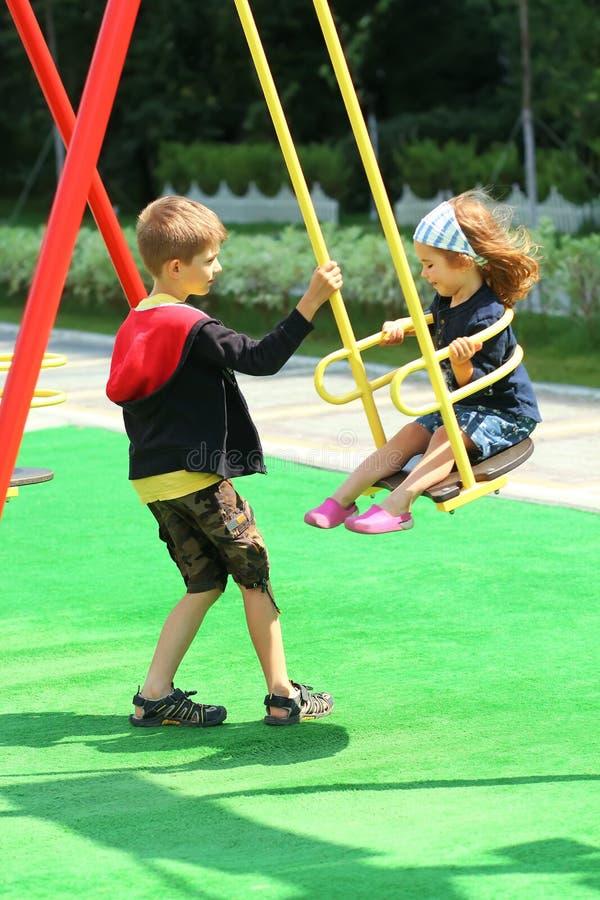 Broder som svänger hans mer unga syster på lekplatsen arkivbild
