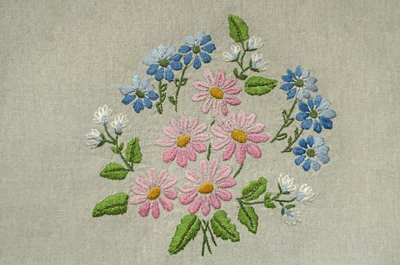 Broderad liten bukett med rosa, blåa och vita blommor med gröna sidor på bomullstyg arkivfoto