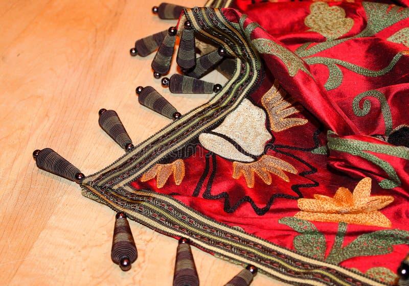 Broderat rikt kulört kast med unika armringar som visas artfully på wood bakgrund royaltyfria foton