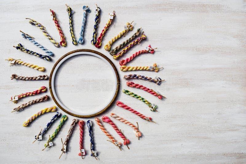 Broderbågen med kanfas och ljusa sy trådar som formas som en sol arkivfoto