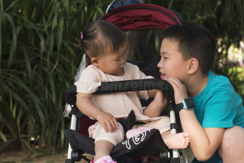 Brodern tar omsorg av den lilla systern behandla som ett barn in bäraren royaltyfri bild