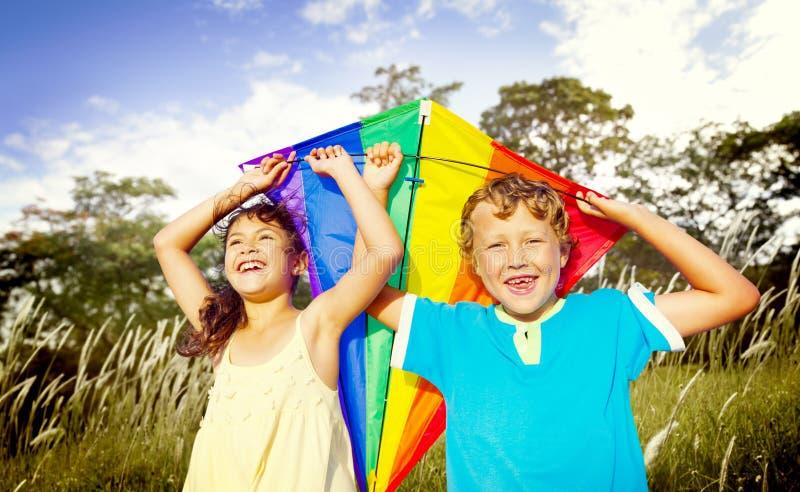 Brodersystern Sibling Playing Kite parkerar begrepp royaltyfri bild
