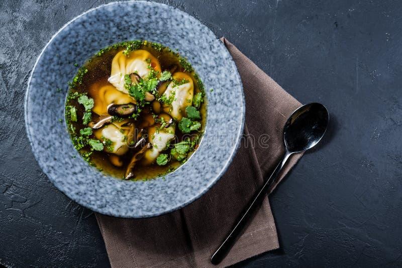 Brodo di pollo del wonton della minestra con i funghi e le erbe, fondo scuro immagini stock