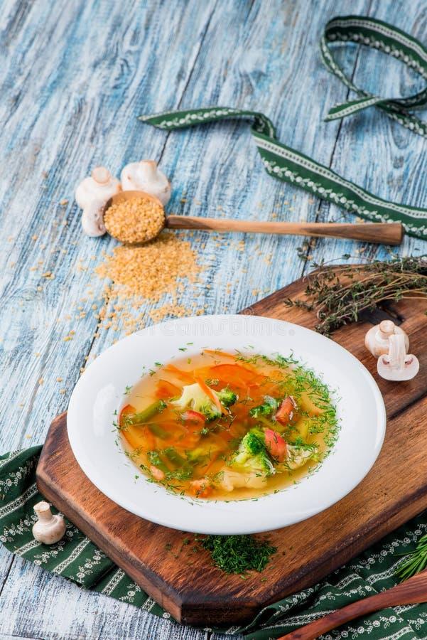 Brodo di verdure, minestra con i broccoli, asparago, carote, cipolle, peperoni dolci e verdi in piatto bianco fotografia stock libera da diritti