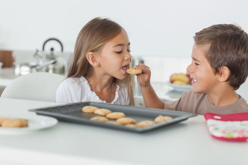 Broer die een koekje geven aan zijn zuster stock afbeeldingen