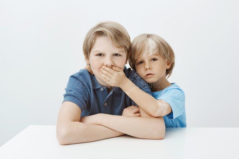 Broer die geheim vragen te houden Portret die van ongelukkige geërgerde jongenszitting bij lijst met gekruiste handen, terwijl fr stock afbeeldingen