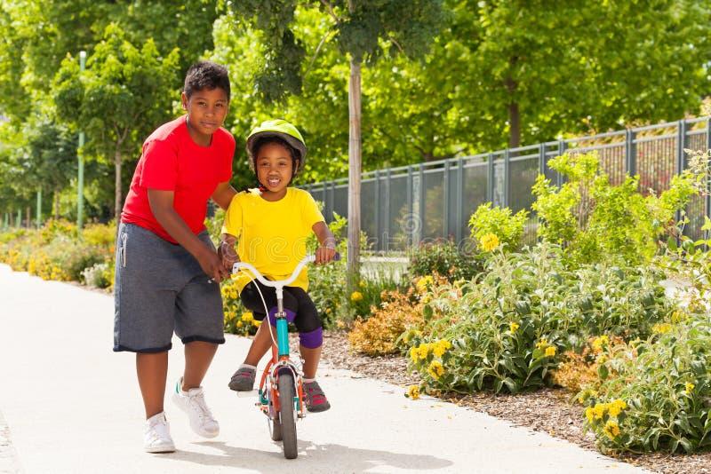 Broer die zijn zuster berijdende fiets helpen bij park stock foto