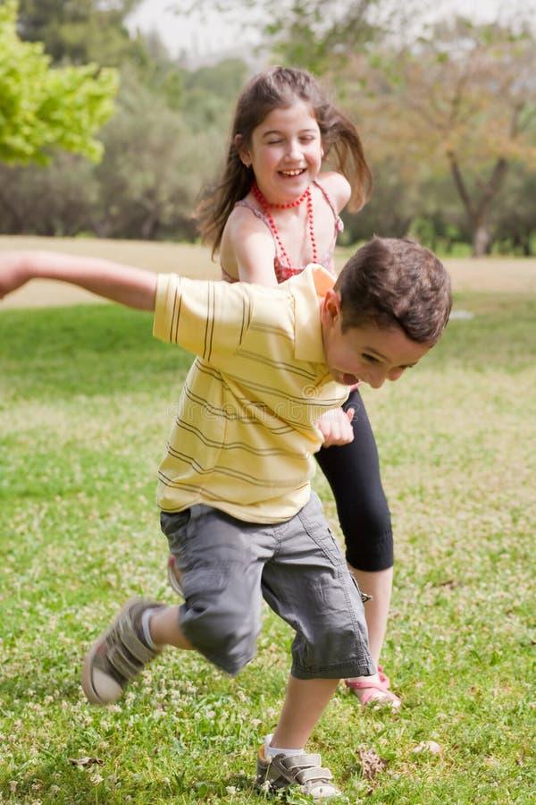 Broer die zijn zuster in het park trekt stock foto