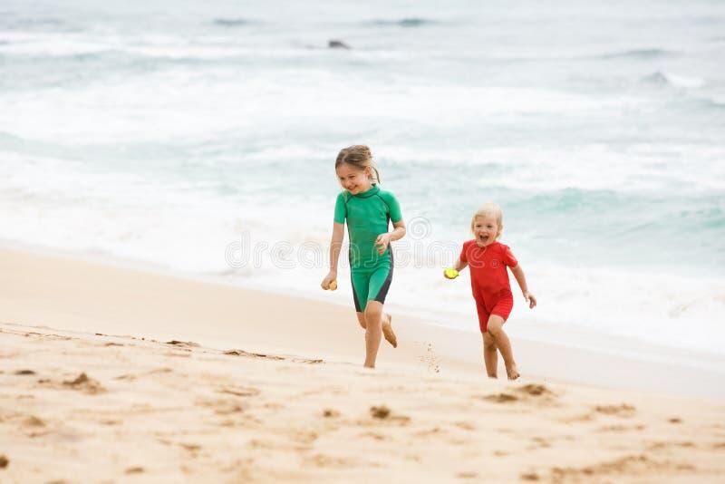 Broer en de zuster die, spelend met zand en water op een tropisch strand, kleedden zich in beschermende wetsuit de lopen stock foto's