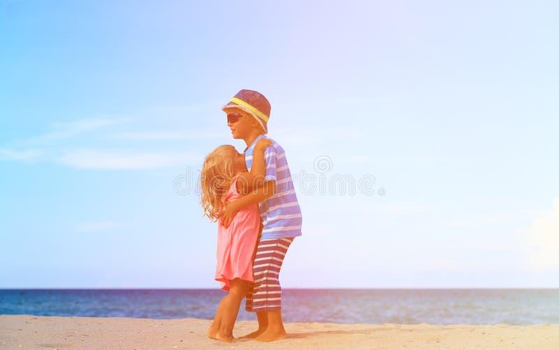 Broer en zuster die bij strand koesteren Siblings vriendschap stock foto
