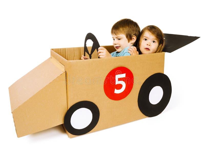 Broer en zuster die een kartonauto drijven stock foto's