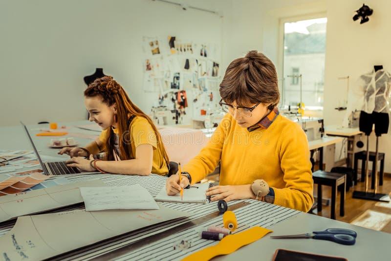 Broer en zuster die heldere gele kleren dragen die schetsen trekken royalty-vrije stock foto