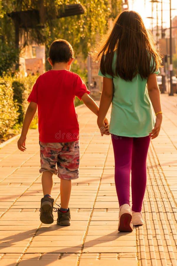 Broer en zuster die onderaan de straat lopen Zusters die handen houden royalty-vrije stock afbeelding