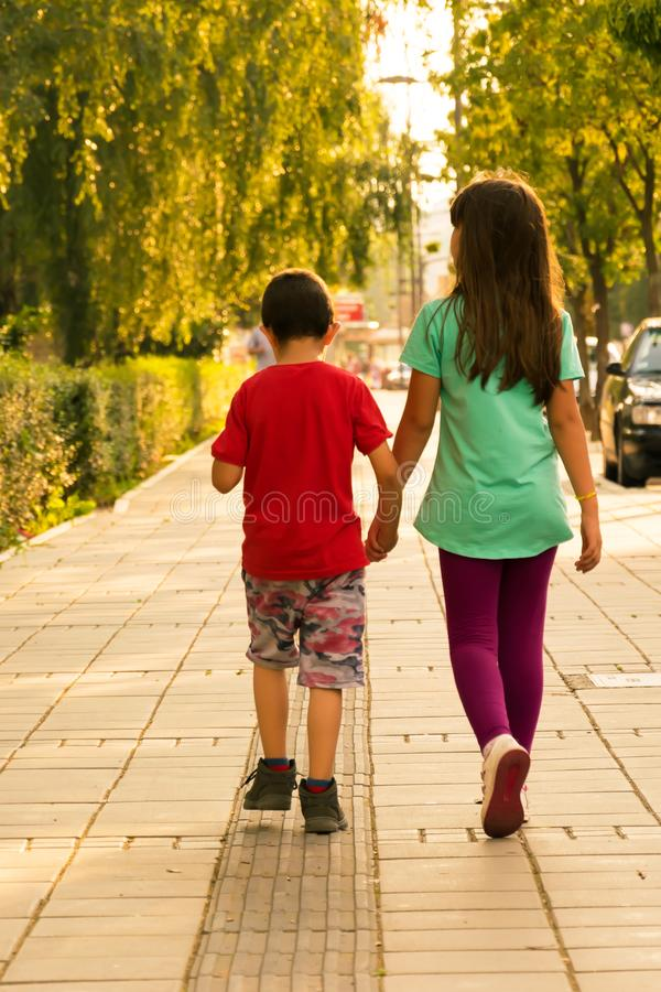 Broer en zuster die onderaan de straat lopen Zusters die handen houden stock foto's