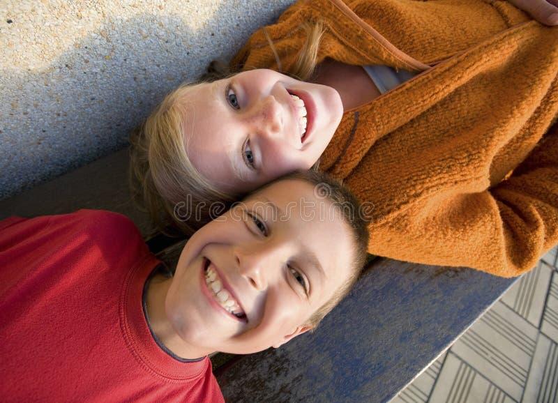 Broer en zuster die op een bank, het lachen liggen royalty-vrije stock foto