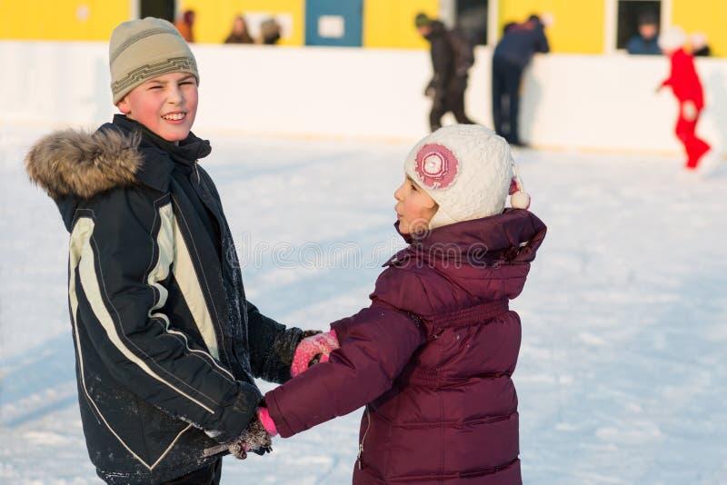 Broer en zuster die op piste hand in hand schaatsen stock afbeelding