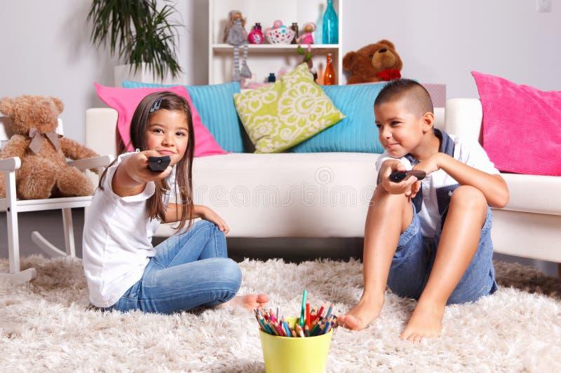 Broer en zuster die op TV letten royalty-vrije stock fotografie
