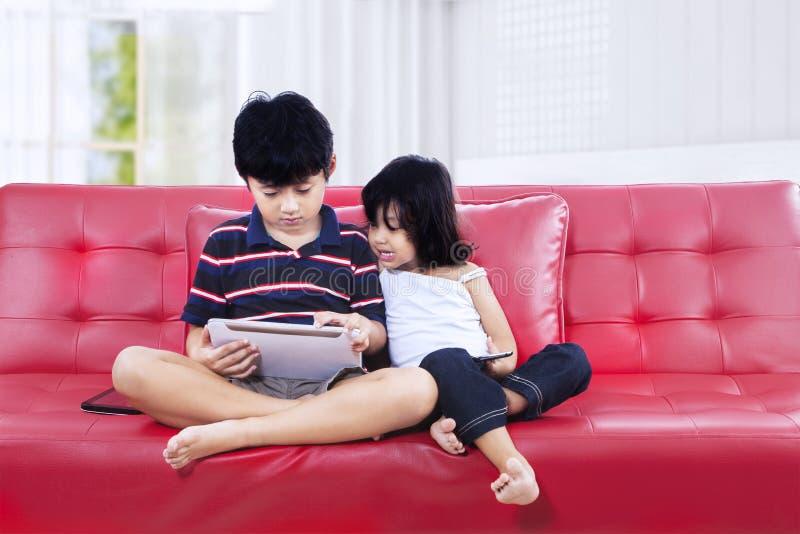 Broer en zuster die tablet op de laag gebruiken royalty-vrije stock foto