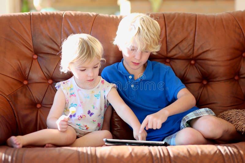 Broer en zuster die tabletpc thuis met behulp van stock afbeelding