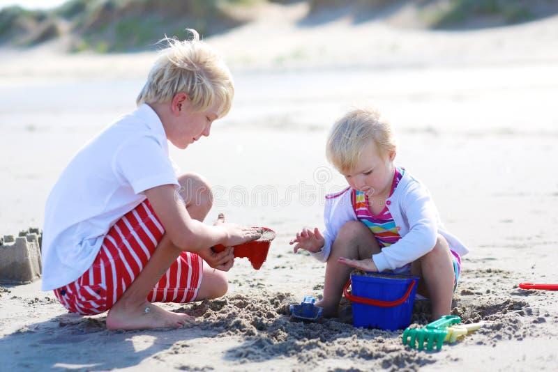 Broer en zuster het spelen met zand op het strand royalty-vrije stock fotografie