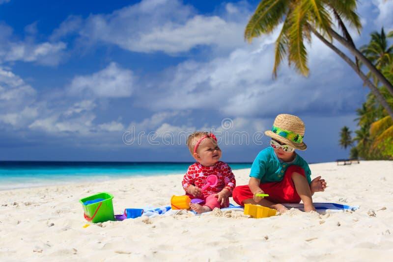 Broer en zuster het spelen op tropisch strand stock foto's