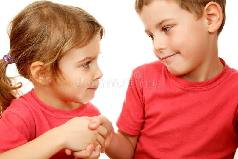 Broer en zuster met de handen van de glimlachschok royalty-vrije stock afbeelding