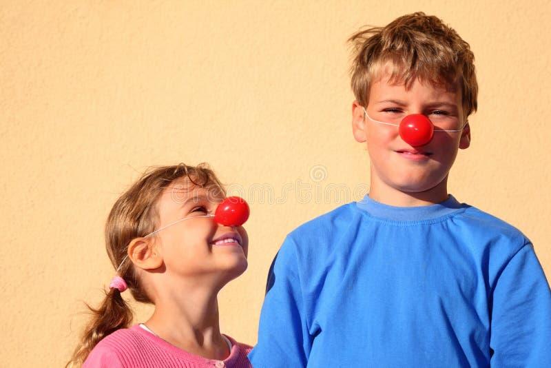 Broer en zuster met de tribune van clownneuzen stock afbeeldingen
