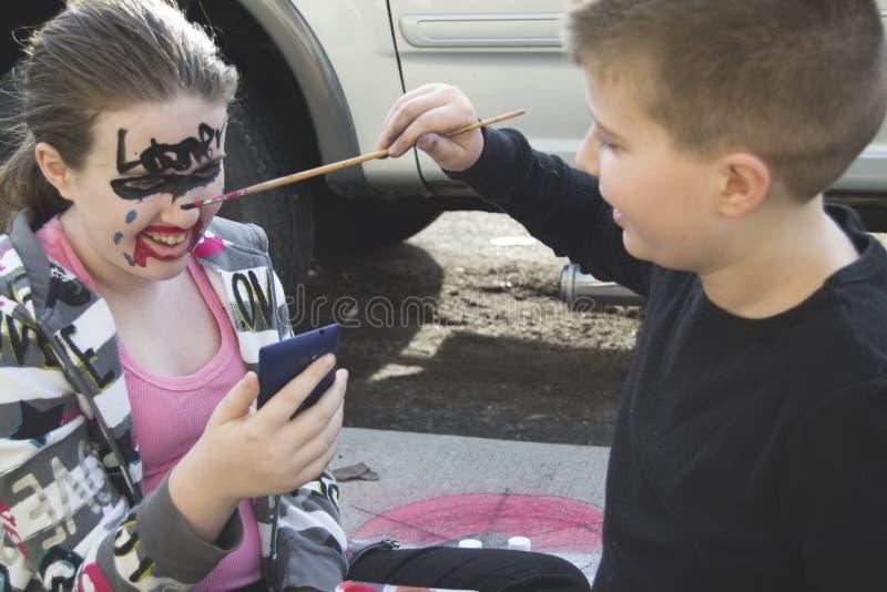 Broer het schilderen zustersgezicht stock afbeelding